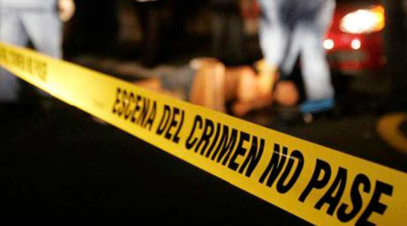 Equipo de medicina legal levantando cuerpo sin vida sobre la carretera, después de un accidente de tránsito y línea amarilla de la Policía Nacional delimitando el área.