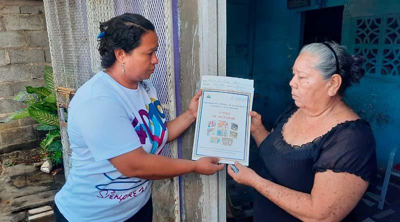 Promotores de la PGR y Juventud Sandinista entregan su título de propiedad a una pobladora de Managua