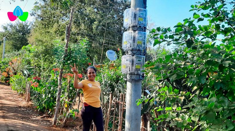 Joven saludando a la par de un medidor de energía eléctrica ubicados en un poste de la comunidad La Montañita de Tisma, Masaya.