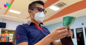 Trabajador del sector educativo con los billetes de su pago en sus manos