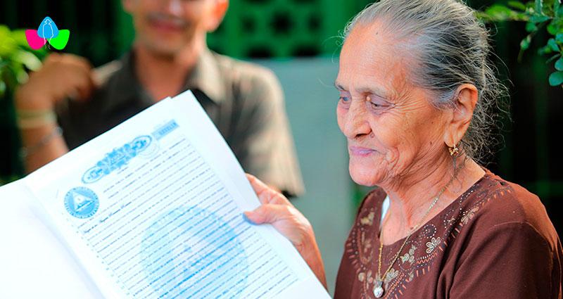 Señora sostiene en sus manos el título de su propiedad, recién entregado por la Procuraduría General de la República de Nicaragua.