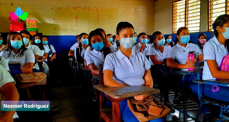 Estudiantes sentados en sus pupitres dentro del salón de clases, listos para iniciar el ciclo escolar