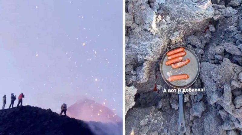 Turistas a la orilla de cráter y asando salchichas en la lava del volcán en Rusia