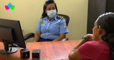 Oficial de la Policía Nacional atendiendo en la Comisaría de la Mujer de Quilalí a una pobladora mujer.