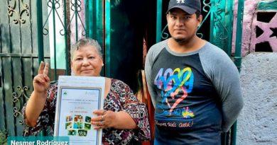 Una de las protagonistas muestra su título de propiedad recibido este miércoles 31 de marzo