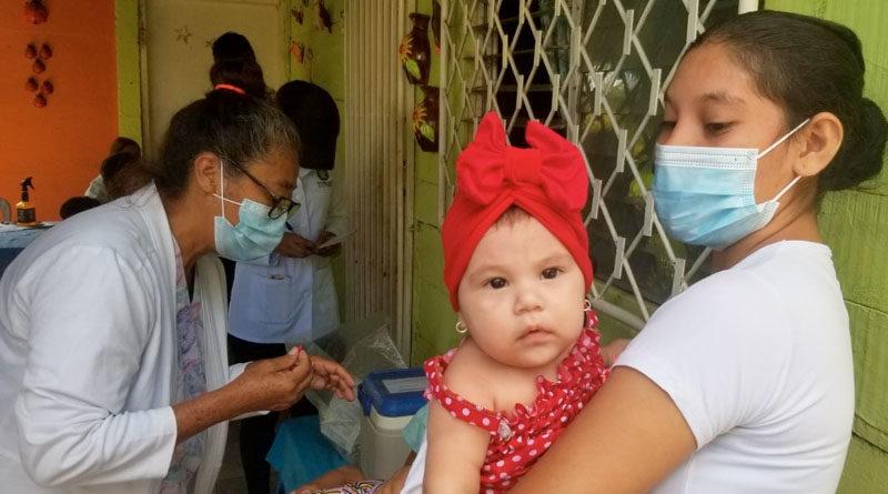 Una mujer sostiene en brazos a una bebé, mientras espera a ser atendida durante la feria de salud en el barrio Frawley