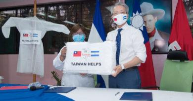 Ministra de Salud, Martha Reyes junto al Embajador de Taiwán, Jaime Chin Mu wu sosteniendo una de las batas
