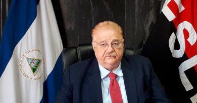 Doctor Paul Oquist en su escritorio y al fondo las banderas de Nicaragua y el Frente Sandinista