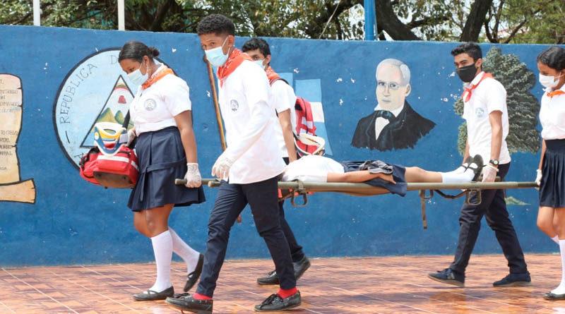Jóvenes del Colegio Salvador Mendieta cargan con una estudiante durante el ejercicio desarrollado