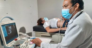 Médico del Ministerio de Salud realiza un ultrasonido a una paciente acostada en una cama