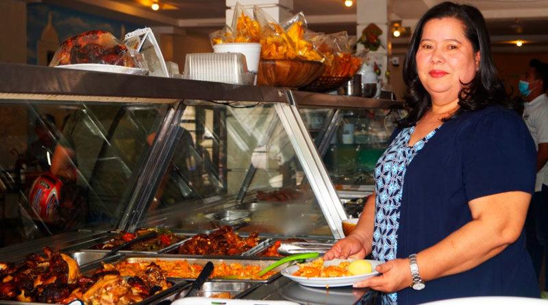 Marlene Reyes, propietaria del restaurante Llamarada del Bosque junto a un exhibidor de comida en su restaurante ubicado en Ocotal, Nueva Segovia