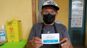 Paciente tras ser vacunado voluntariamente contra el Covid-19, muestra el carné emitido por el Ministerio de Salud