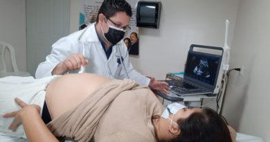 Médico especialista del MINSA realiza ultrasonido a una mujer embarazada acostada en una camilla