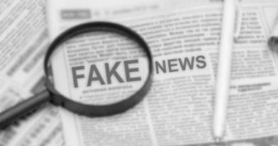Lupa enfocando las noticias falsas en un periódico