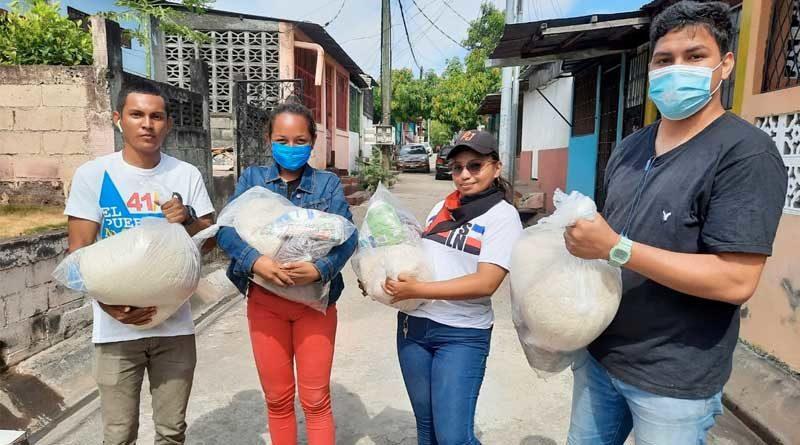 Miembros de UNEN y Juventud Sandinista sosteniendo paquetes alimenticios que fueron entregados a madres de héroes y mártires en Managua