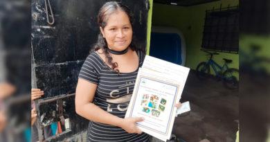 Una mujer muestra el título de propiedad recibido