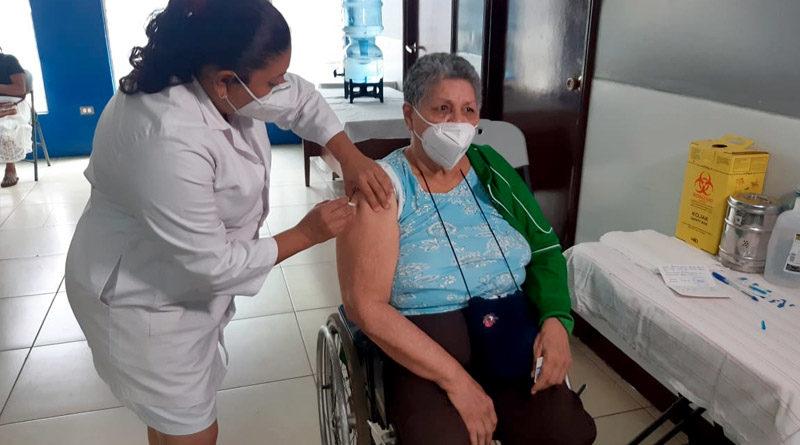 Médica del Ministerio de Salud aplica vacuna contra el Covid-19 a una señora en silla de ruedas