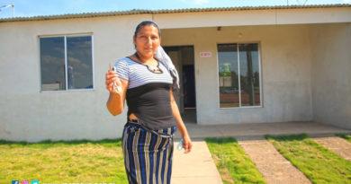 Una mujer muestra las llaves de la vivienda recibida en Villa Santiago