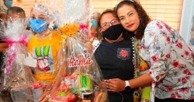 Alcaldesa de Managua, Reyna Rueda, abrazando y entregando regalo a una madre que asiste al Centro de Medicina Natural de Managua.