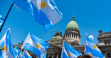 Banderas de Argentina siendo ondeadas por personas congregadas en la Plaza del Congreso de Argentina, ubicada en la Ciudad de Buenos Aires