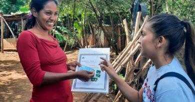 Habitante de la comarca El Portillo en el municipio de Nindirí, departamento de Masaya, recibiendo su titulo de propiedad de manos de una joven miembro de Promotoría Solidaria de la Juventud Sandinista.