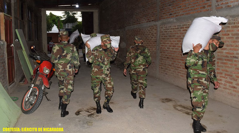 Efectivos militares del 1 Comando Militar Regional descargando los 330 quintales de semilla de frijol, en la bodega ubicada en el barrio Boanerges López, de la ciudad de Estelí.
