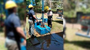 Dos hombres trabajan en el motor de la bomba de un pozo de agua