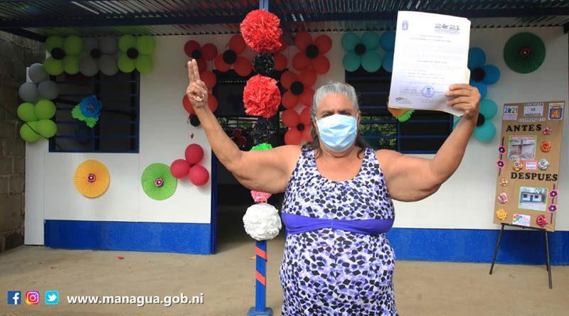 Señora que recibió la nueva vivienda, levanta las manos mostrando las llaves de su hogar