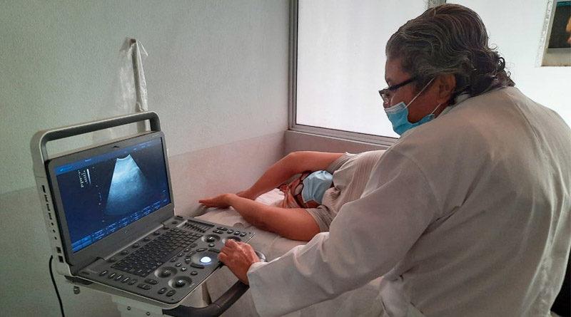 Doctora del Centro de Salud Francisco Morazán realiza ultrasonido a una mujer acostada en una cama