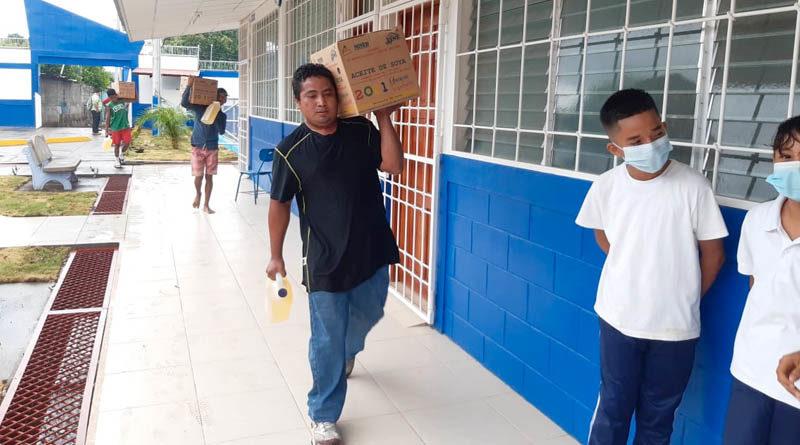 Hombres cargan cajas de aceites, parte de la Merienda Escolar entregada este martes 04 de mayo