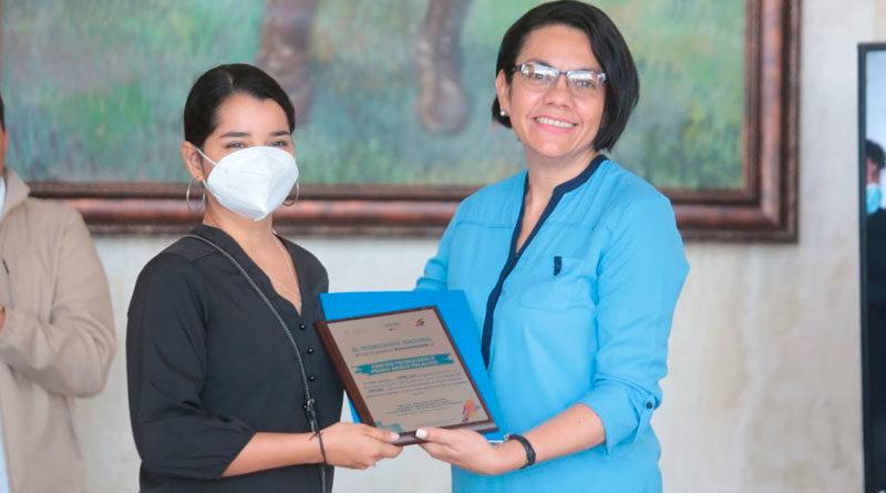 Loyda Barreda, directora ejecutiva del INATEC, entregando premio y reconocimiento a estudiante ganadora de Tercer Concurso de Artes Visuales