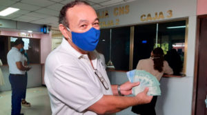 Trabajador del Ministerio de Salud mostrando su salario que acaba de retirar en unas de las cajas habilitadas en el complejo de salud Concepción Palacios de Managua, Nicaragua.