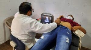 Paciente sobre una camilla es atendida por un médico, quien realiza un ultrasonido durante la feria de salud en el barrio Hiealeah
