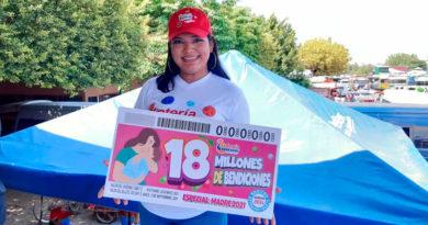 Trabajadora de Lotería Nacional de Nicaragua sostiene cartel del sorteo en homenaje al día de las madres nicaragüenses