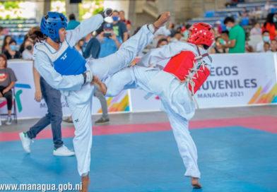 Dos jóvenes peleando durante el inicio del taekwondo en los Juegos Juveniles Managua 2021