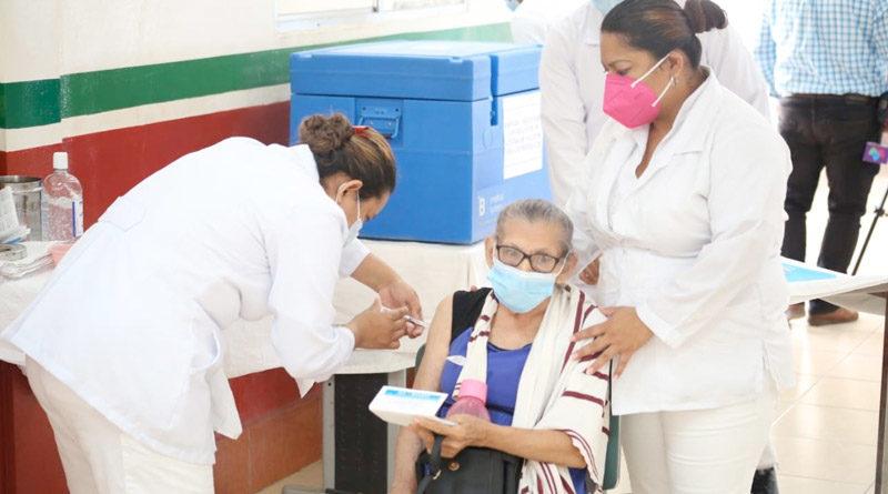 Doctoras del Ministerio de Salud vacunan a una anciana en silla de ruedas