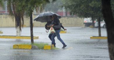 Dos personas bajo la lluvia cubriéndose con un paraguas
