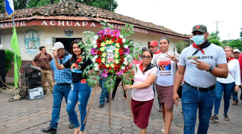 Familias de Achuapa llevando ofrendas florales al monumento dedicado a los Héroes y Mártires
