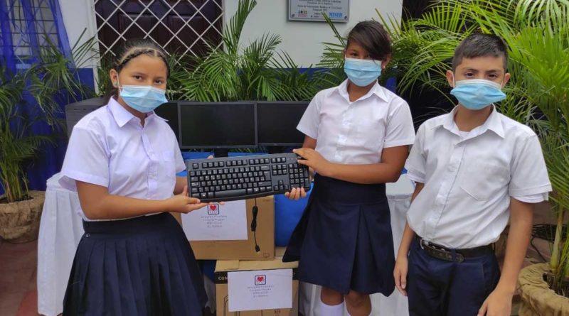 Niños estudiantes sosteniendo un teclado de computadora
