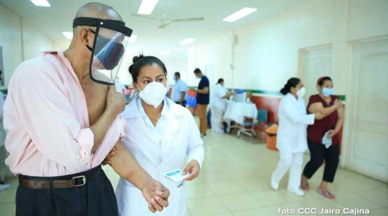 Paciente junto a enfermera después de vacunarse contra la covid-19