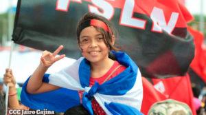 Jovencita saludando con la bandera de Nicaragua y el Frente Sandinista en su espalda