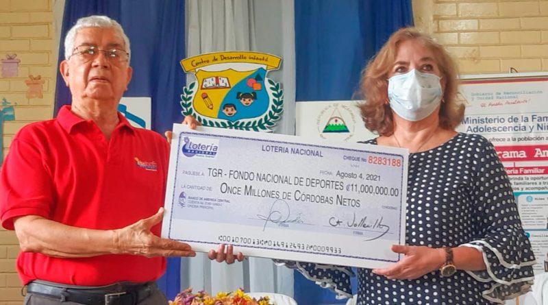 Gerente General de la Lotería Nacional, Ernesto Vallecillo haciendo entrega de cheque de utilidades al Ministerio de la Familia y al IND.