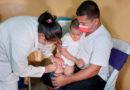 Personal médico del Ministerio de Salud aplica vacuna a un menor de edad cargado en brazos por su padre