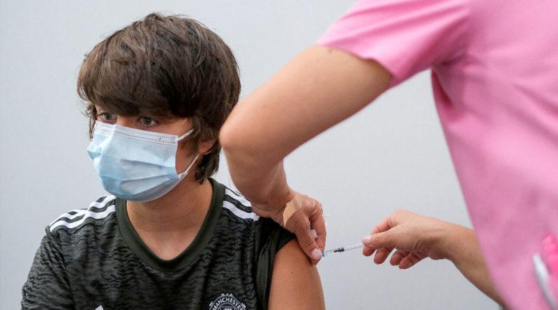 Personal médico aplicando vacuna a un menor de edad