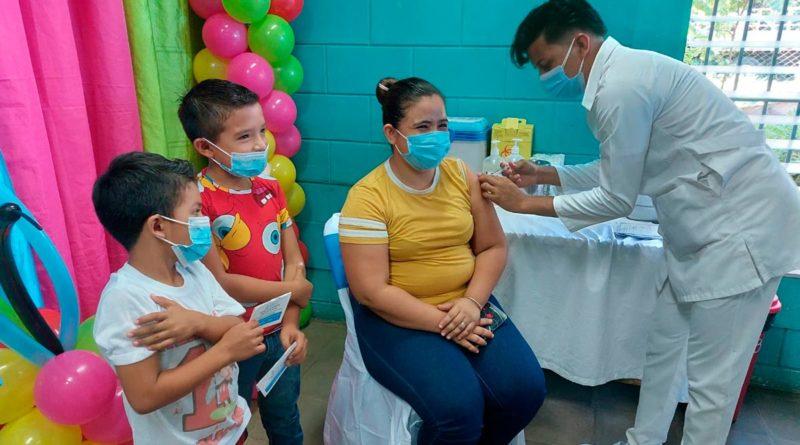 Madre de familia con sus hijos menores siendo vacunada contra la COVID-19 en Managua